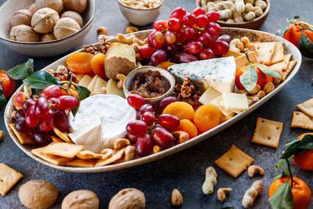 Big plate with appetizer assortment  Grape  cheese  nuts  jam and bread