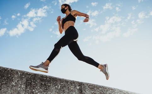 Sporty woman doing running workout with face mask