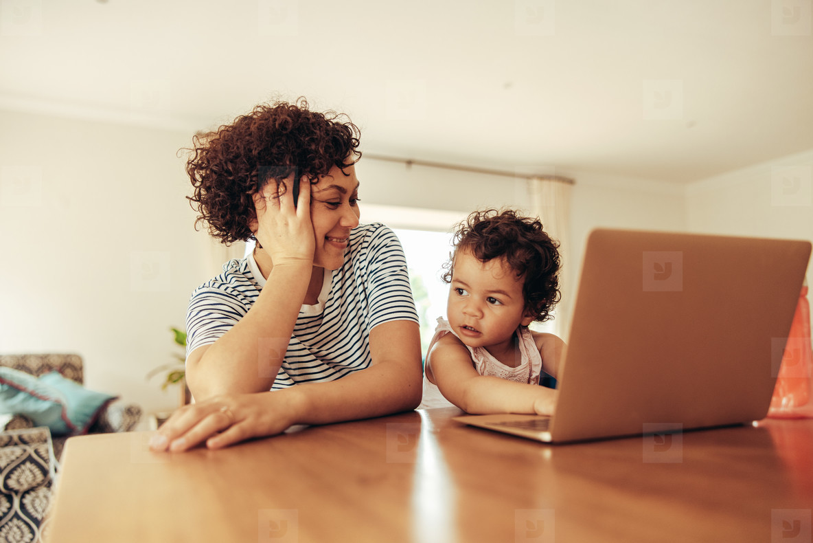 Mother watching baby pretending working on laptop