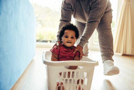 Happy child enjoying laundry basket ride at home