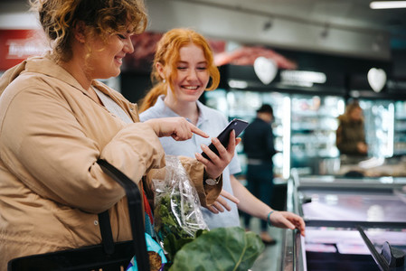 Shopper asking supermarket worker for help finding a food item