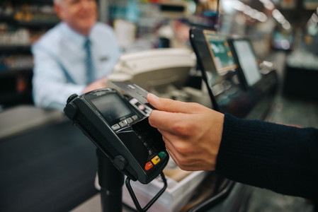 Customer making contactless payment at supermarket