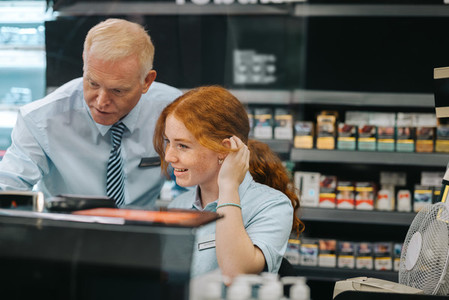 Manager giving training to a new employee at supermarket