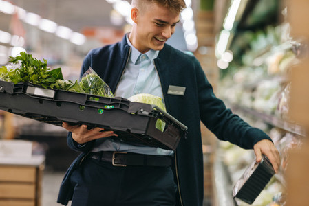 Man working in the supermarket produce section