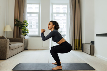 Side view of a fit woman doing sit ups on mat