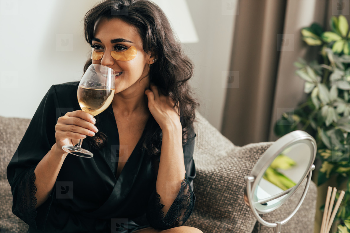 Brunette woman with eye patches drinking wine