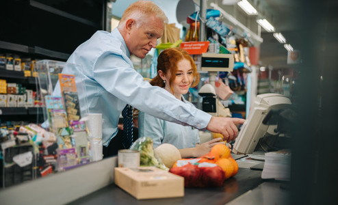 Grocery store manager training a new employee