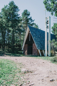 a church with nothing around in the middle of a hiking trail surrounded by trees and bushes