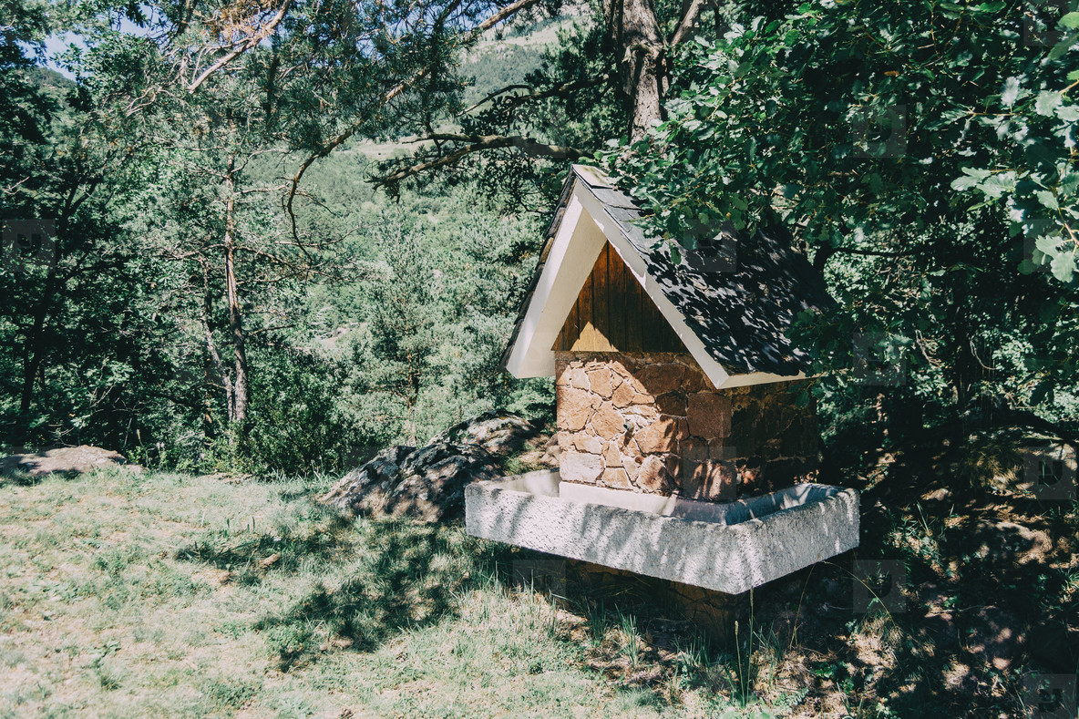 A house shaped fountain in the middle of a hiking trail in a forest in Catalonia  Spain