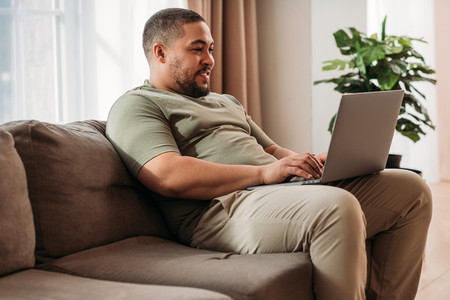 Smiling man with laptop on his hips sitting on a sofa