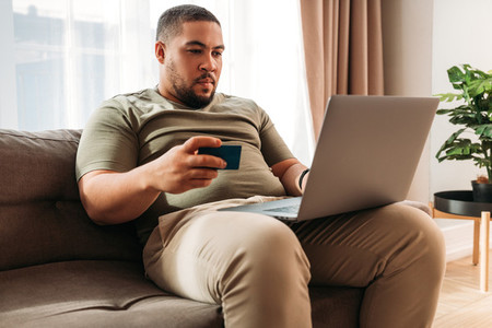 Young man paying online with a credit card at home