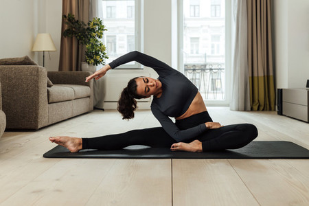 Fit woman in sportswear exercising on mat in a living room