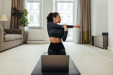 Woman sitting on a mat in front of a laptop warming up hands