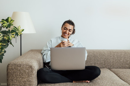 Young smiling woman holding a cup while sitting on a sofa