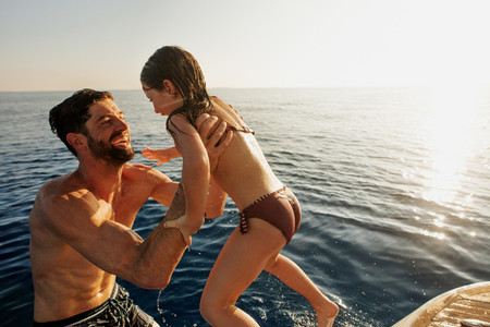 Father playing with his daughter in the sea