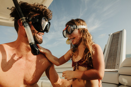 Man with kid sailing on yacht wearing diving masks