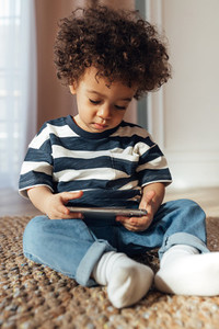Little boy sitting indoors with a smartphone in his hands