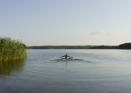Boy swimming in sunny tranquil lake