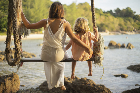 Mother and daughter on large rope swing over ocean