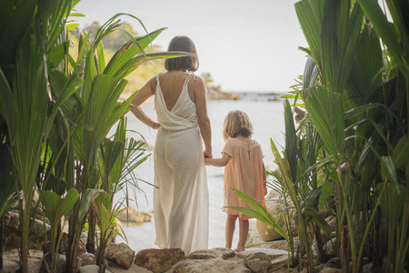 Mother and daughter holding hands on tropical beach