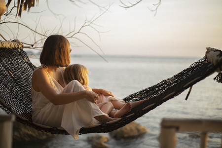 Serene mother and daughter in hammock enjoying ocean sunset