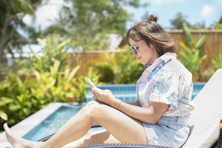 Woman using smart phone on sunny poolside lounge chair