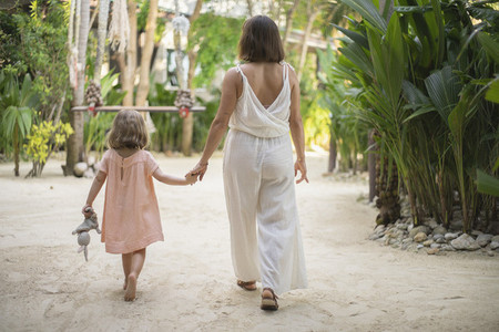 Mother and daughter holding hands walking at tropical resort