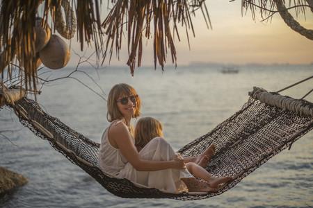Portrait mother and daughter in hammock enjoying ocean sunset