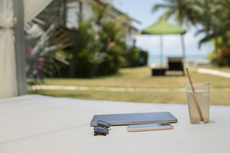 Coconut water sunglasses smart phone and notebook on cabana bed