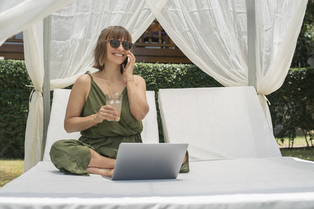 Happy woman talking on smart phone at laptop in cabana