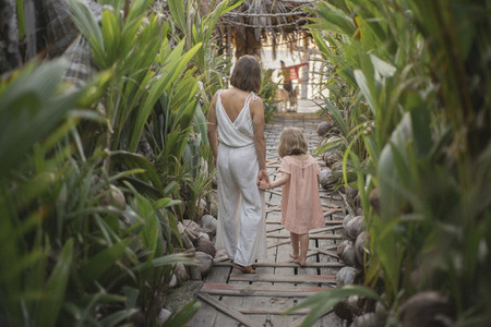 Mother and daughter holding hands on tropical resort boardwalk