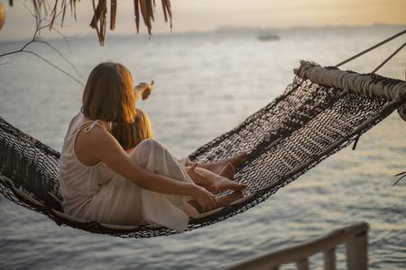 Mother and daughter in hammock enjoying ocean sunset