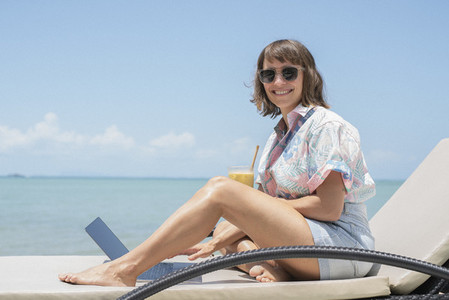 Portrait happy woman with cocktail and laptop on sunny beach lounge chair