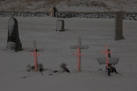 Red light crosses on snowy cemetery gravestones