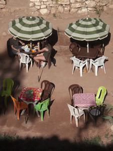 People dining under umbrella at sunny cafZ