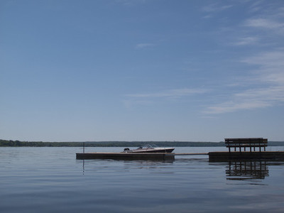 Boat moored alongside tranquil dock on blue lake