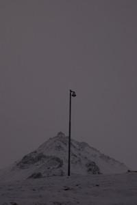 Street lamp against snowy mountain
