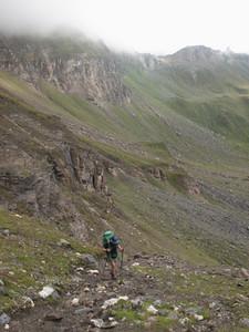 Woman trekking up rugged mountain