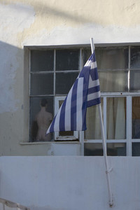Greek flag on flagpole outside window with mannequin