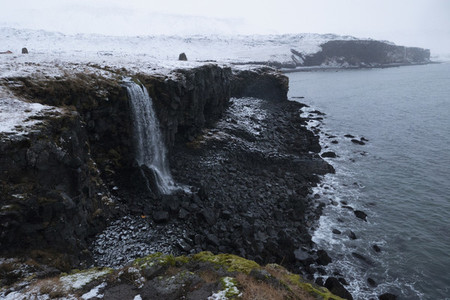 Majestic snowy waterfall over ocean cliff