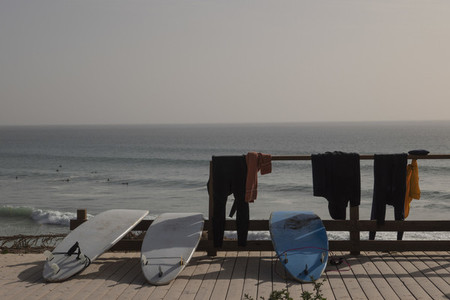 Surfboards and wetsuits drying on sunny beach boardwalk