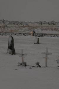 Snowy cemetery gravestones and crosses