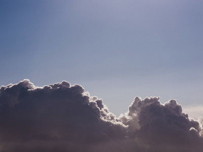 Fluffy cumulus clouds in sunny blue sky