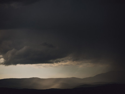 Dark gray storm clouds over silhouetted hills