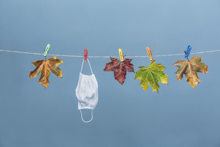 Face mask hanging on clothesline with autumn leaves