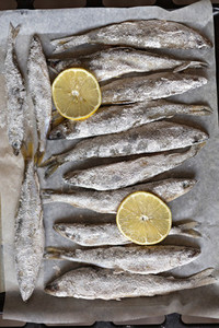 Salted whole fish and lemon slices on parchment paper