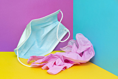 Crumpled face mask and plastic gloves on colorful background