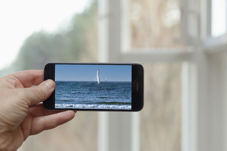 POV Person looking at photo of sailboat and ocean on smart phone screen