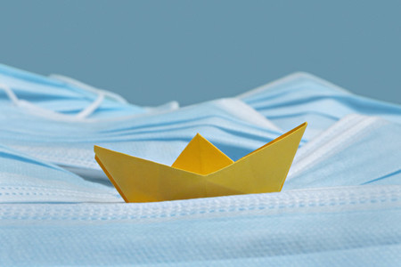 Yellow origami boat on disposable blue face masks