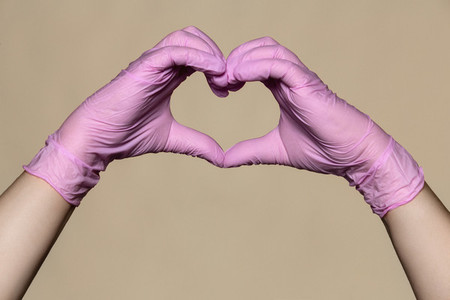 Hands in pink protective gloves forming heart shape